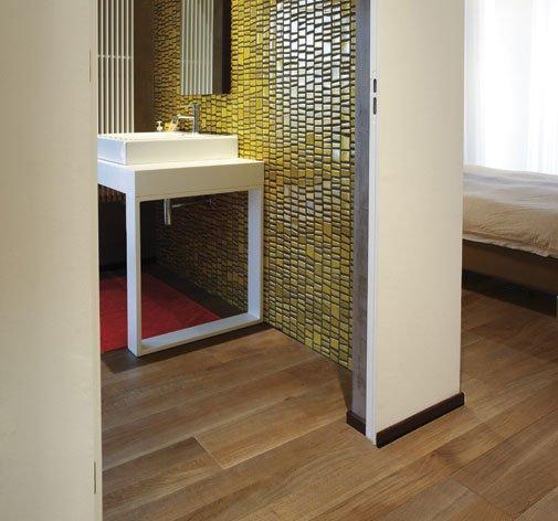 un pavimento in parquet e vista di un lavabo in un bagno con pareti piastrellate gialle e nere