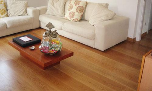 una sala con un tavolino, un divano bianco e un pavimento in parquet