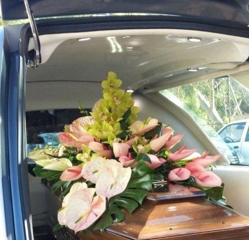 Bara all'interno del carro funebre con la porta aperta e possiamo vedere i fiori che lo coprono