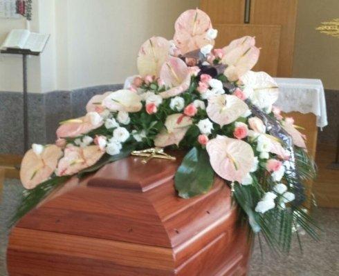 Bara di legno mogano con crocifisso e coperto di fiori