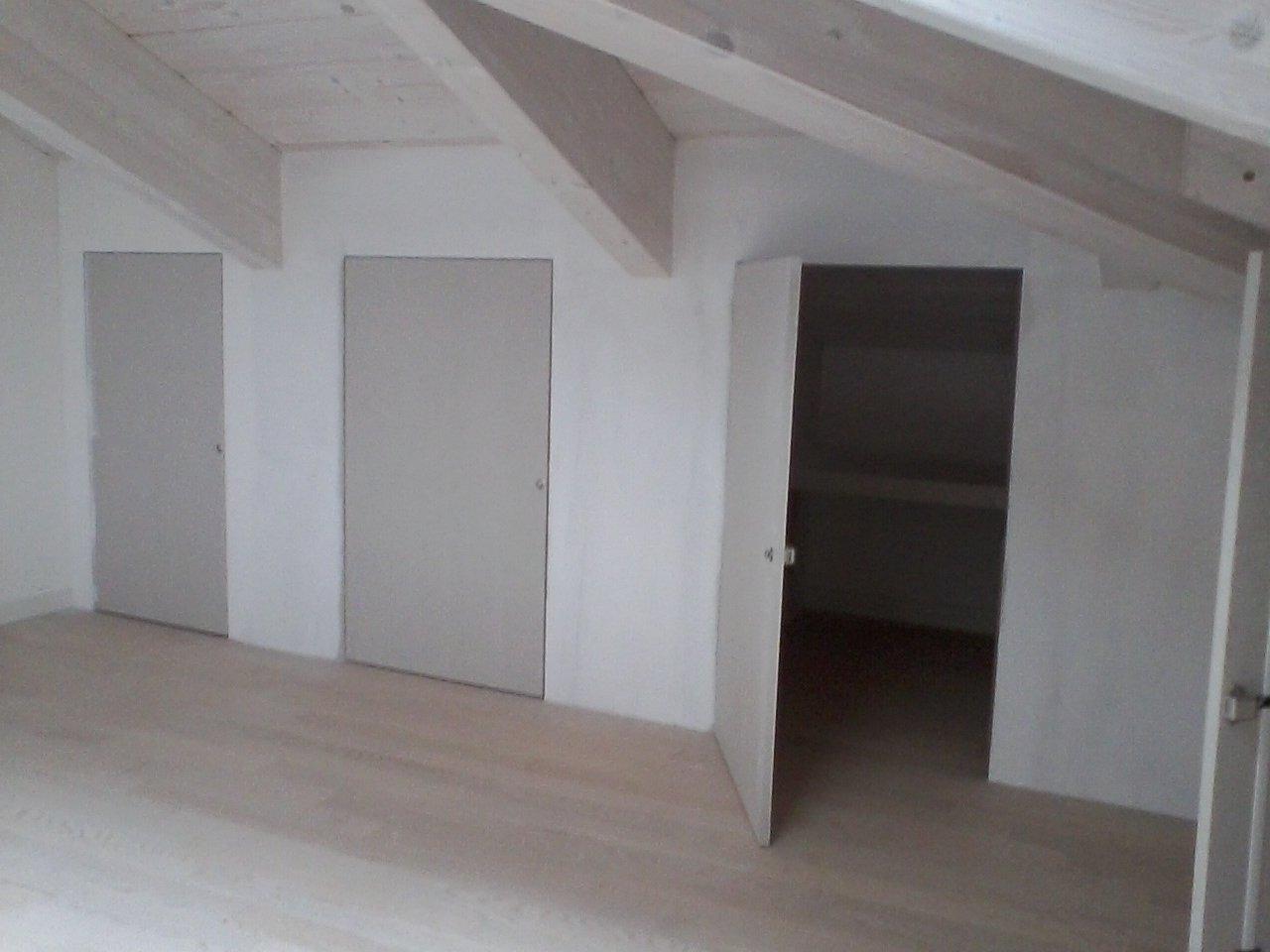 tre porte di cui una aperta in un sottotetto