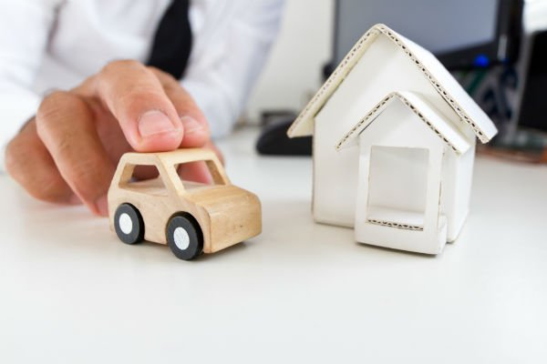 Businessman holding a wooden car on a table.