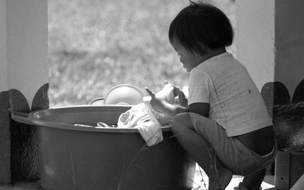 bambina asiatica lava i panni