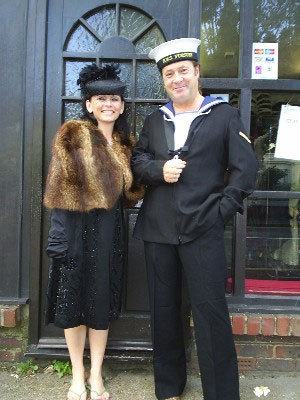 A man dressed as a sailor, arm in arm with a lady dressed 40s style with black dress and fur stole