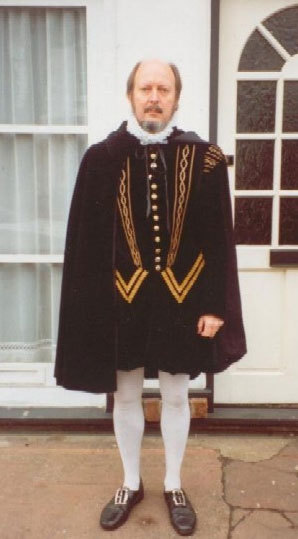 A man in Tudor style cape and white tights with buckle shoes