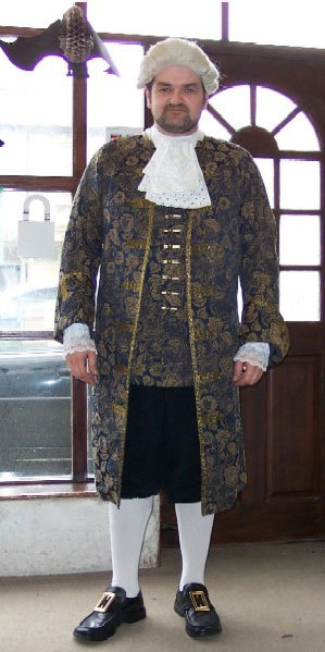 A man in period dress with brocade coat, buckle shoes and white cravat