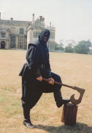 A man wearing a black wood-cutter costume with black hood and mask