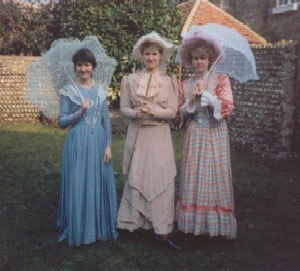Three ladies in long dresses with parasols