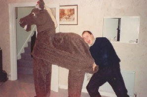A man standing behind a pantomime horse
