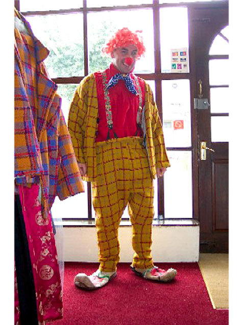 A clown in yellow and red check suit, red shirt, red wig and big pointy shoes