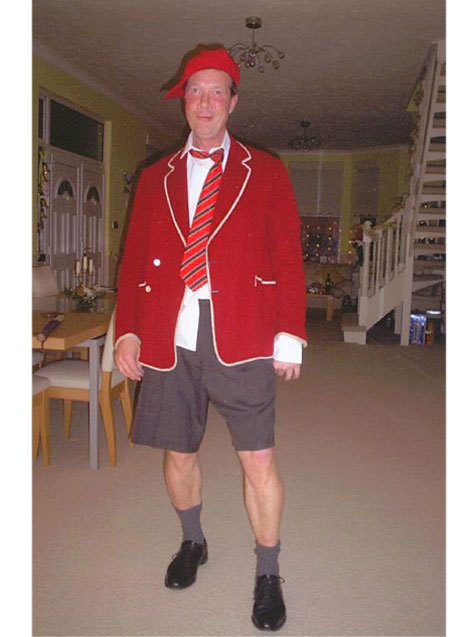 A man dressed as a schoolboy in shorts, red blazer, red stripe tie and red cap