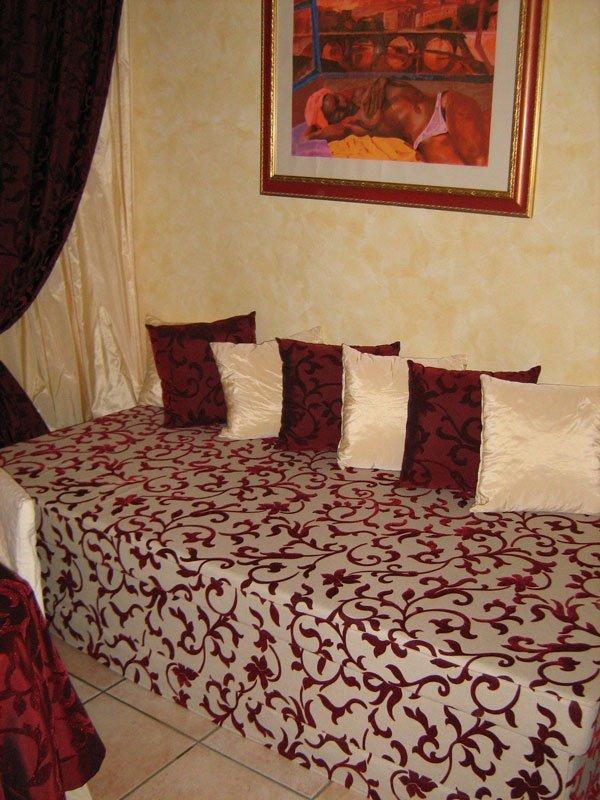 Un divano rivestito con una stoffa con disegni a fiori di color rosso e grigio