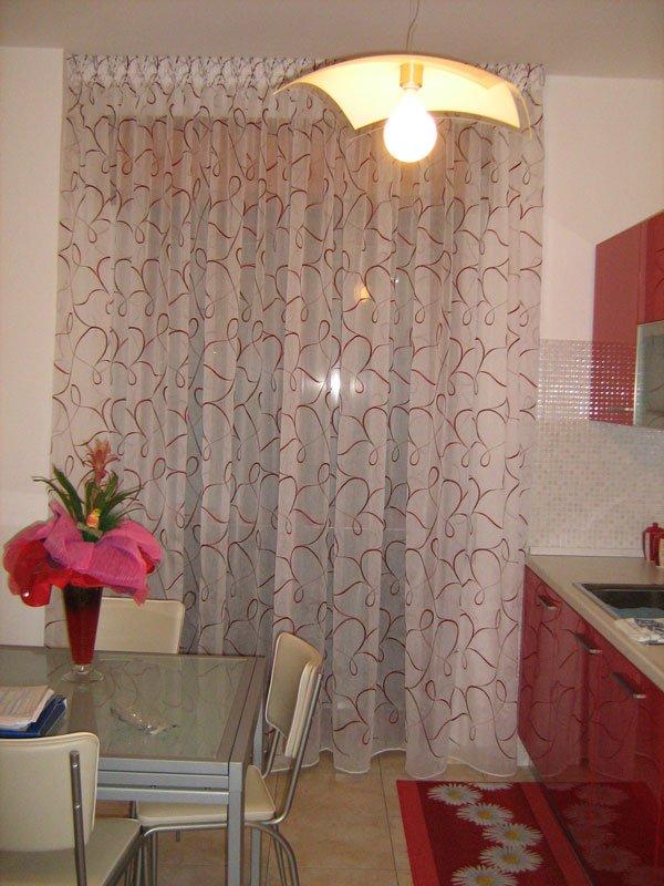 Un tavolo sulla sinistra e sulla destra un mobile da cucina di color rosso e delle tende di color bianco e rosso
