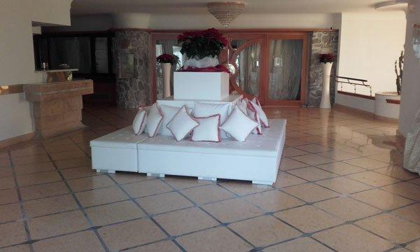 Un divano di pelle di color bianco con dei cuscini di color bianco