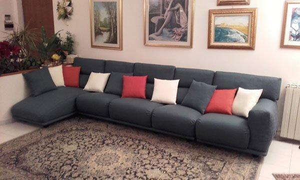 Un divano angolare di color grigio scuro con dei cuscini di color rosso e bianco