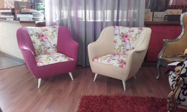 Due poltrone rivestiti con stoffe di color fucsia e beige con disegni di fiori