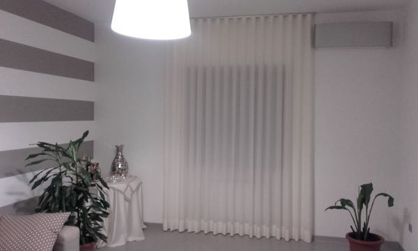 Delle tende lunghe di color bianco e una lampada a sospensione