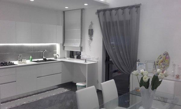 Una cucina con dei mobili di color bianco e delle tende di color grigio