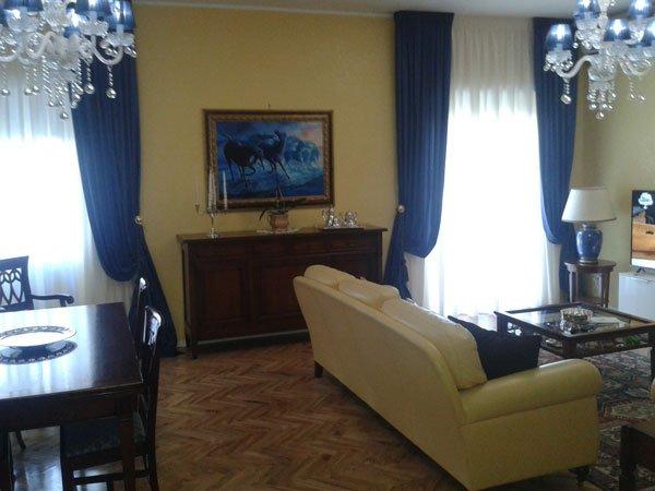 Una sala con un divano di color beige e delle tende di color blu