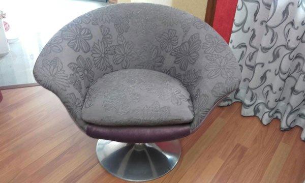 Una poltrona a forma di conchiglia di color grigio con disegni a fiori
