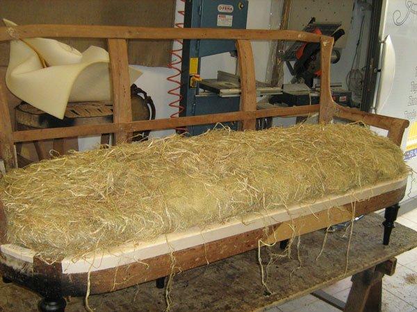 Una struttura in legno di un divano riempito con della paglia prima di rivestimento