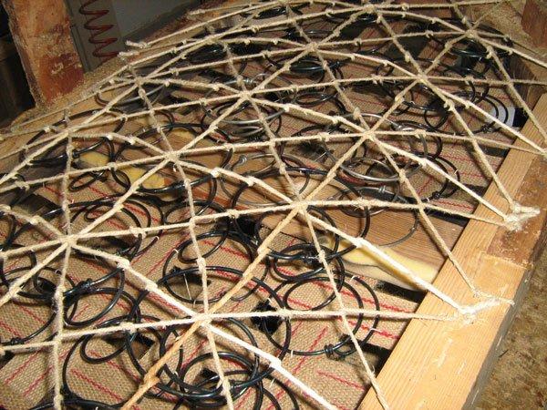 Una struttura in legno con delle doghe e delle molle e legati con un cordino
