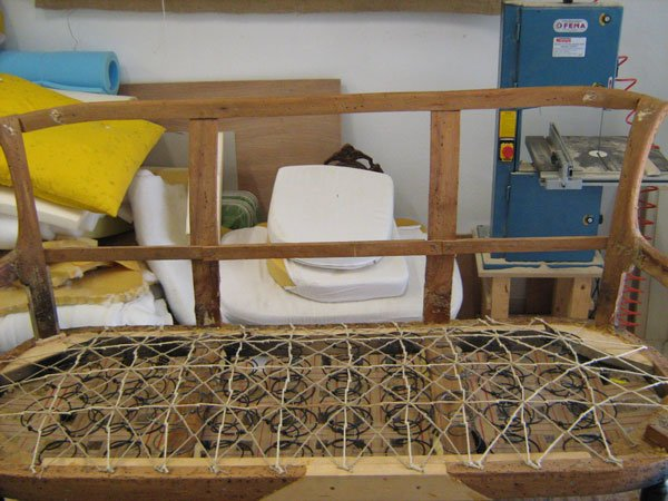 Una struttura in legno con delle doghe e delle molle e legati con un cordino e dietro altro materiale