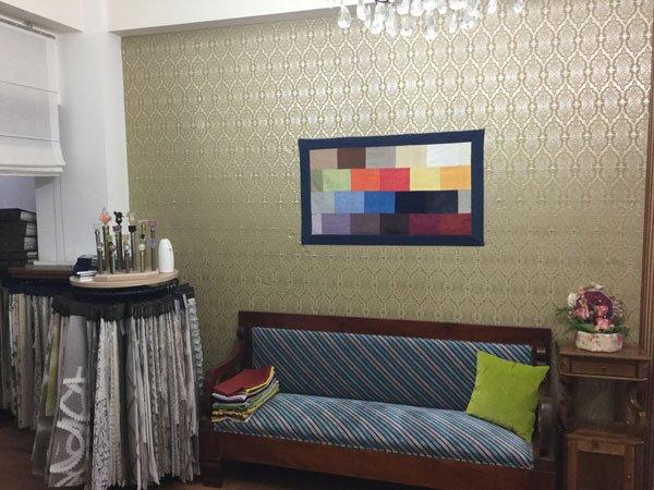 un salotto con un divano ricoperto con cuscini a righe azzurre e rosse, un cuscino verde e una tappezzeria color champagne e un quadro al muro