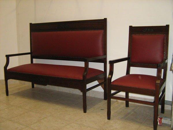 Un divano e una poltrona in legno con cuscini ricoperti in pelle di color bordeaux