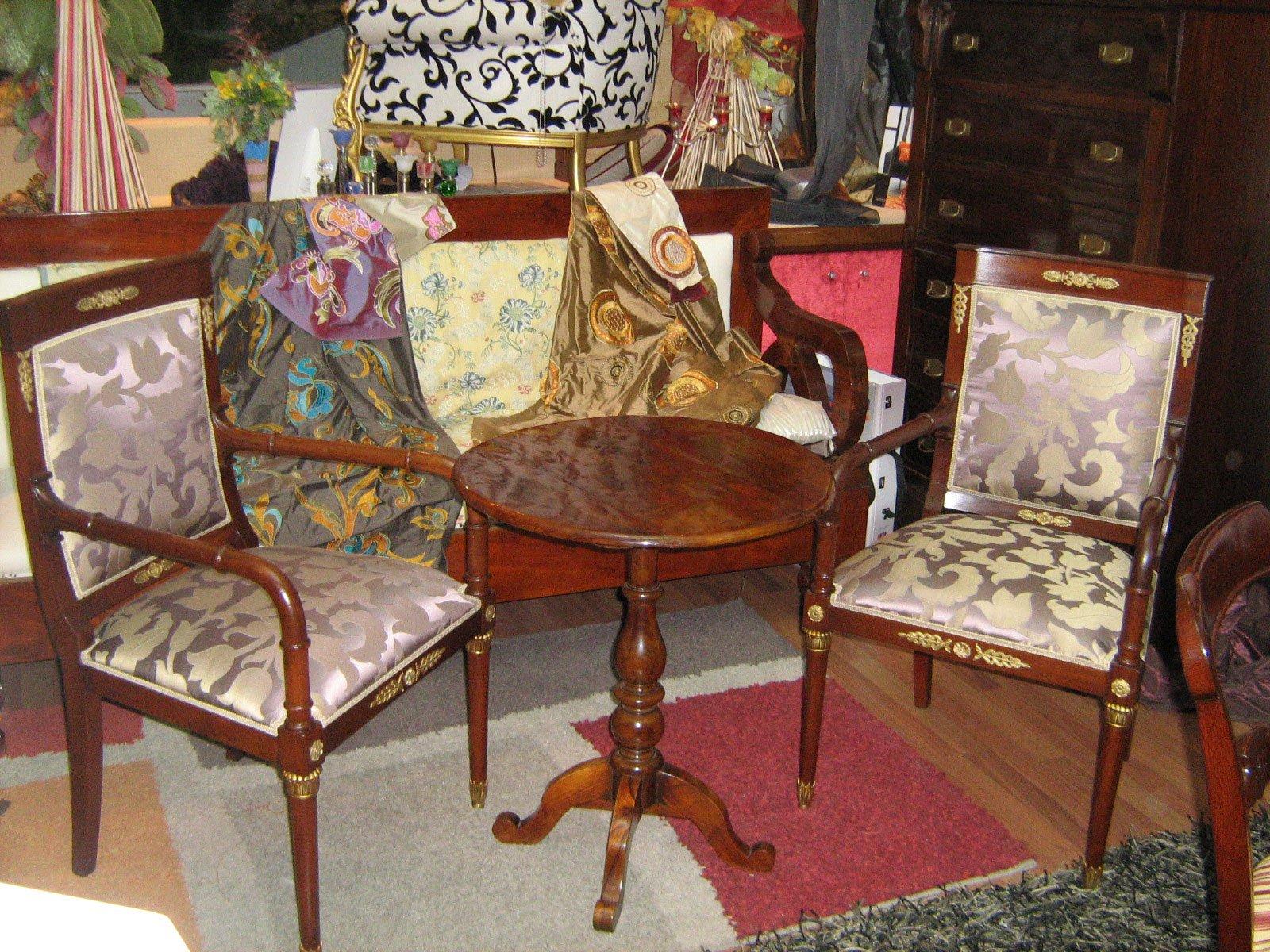 un tavolino e due poltrone di legno tappezzate
