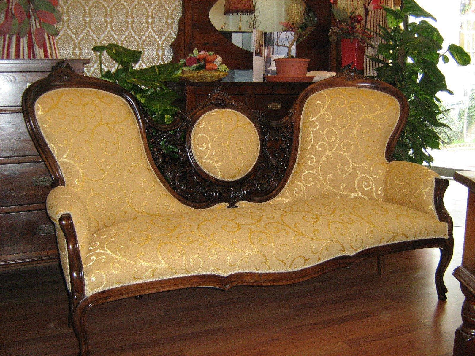 Un divano in legno con dei cuscini ricoperti in color beige