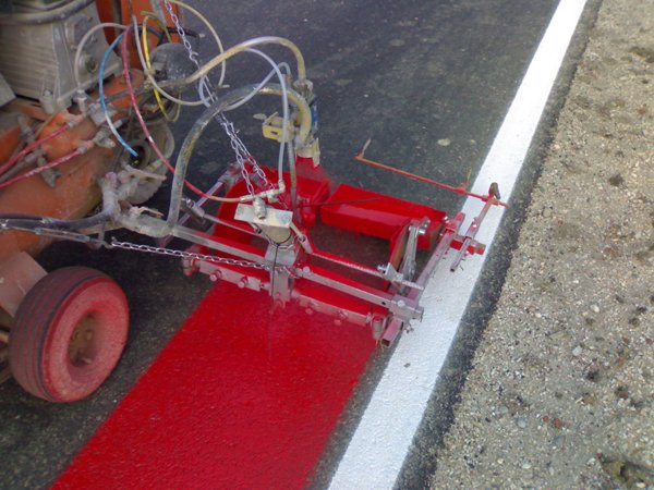 macchinario mentre effettua una striscia di vernice rossa per la ciclabile