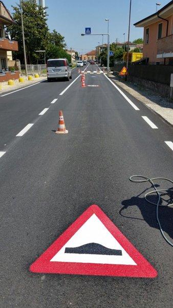 strada asfaltata con cartello pericolo dossi