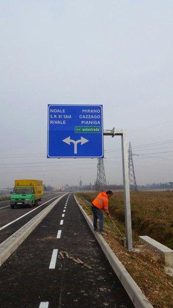 operaio pulisce la strada sotto a un cartello stradale