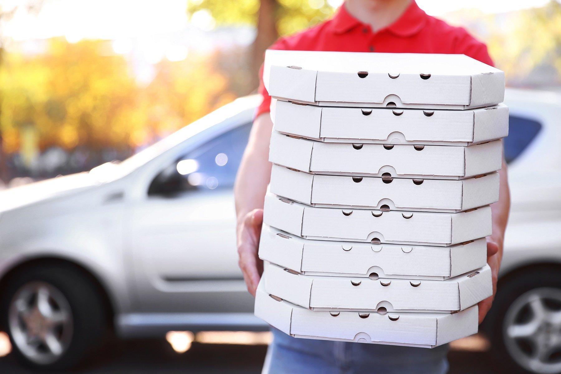 Pizza Delivery ragazzo in possesso di scatole di pizza vicino auto