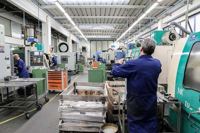 operaio di spalle lavora in una officina macchine