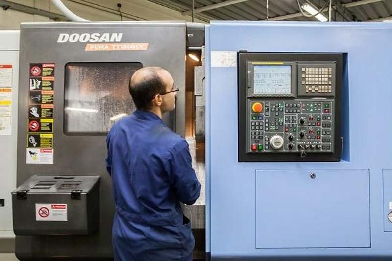 operaio controlla il settaggio di una macchina automatica