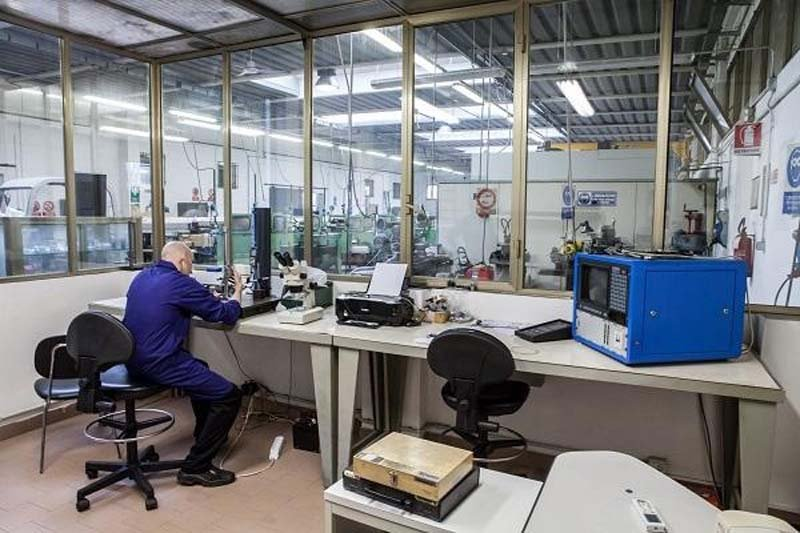 operaio mentre lavora con portatile in una officina macchine