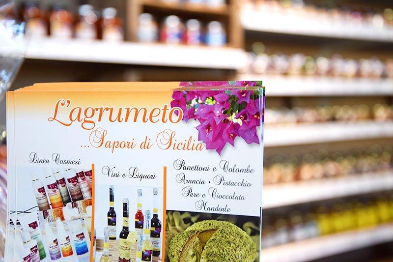 un depliant con scritto L'agrumeto Sapori di Sicilia e dietro vista di scaffali con dei prodotti