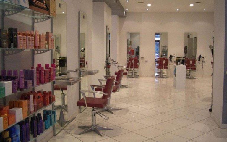 vista laterale di un salone per parrucchieri e assortimento prodotti per la cura dei capelli