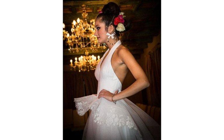 vista laterale di una modella con abito da sposa rosa e chignon in testa