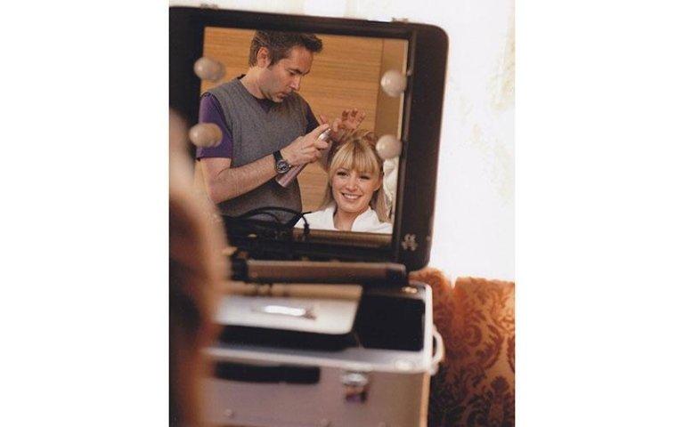 parrucchiere durante un`acconciatura a una sposa