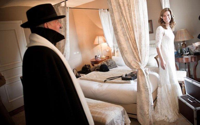 sposa sorride a un uomo vestito di nero con sciarpa bianca