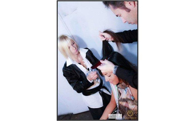 parrucchiere taglia i capelli a una modella con vicino una truccatrice