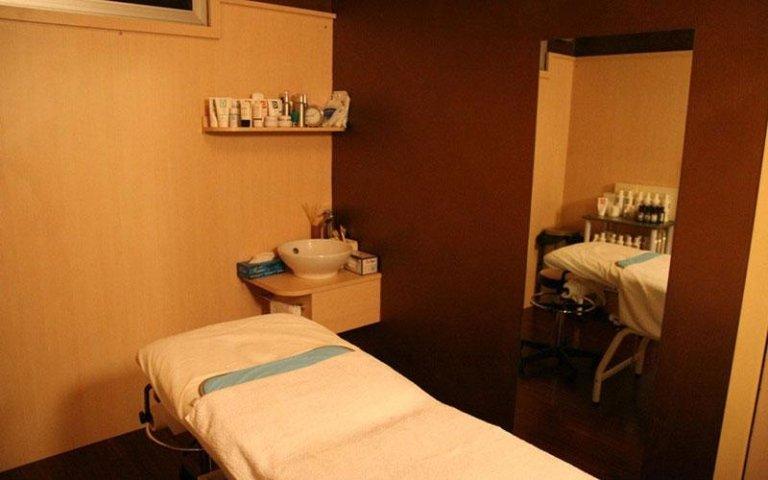 lettino per massaggi con lavabo e scaffale con prodotti per la cura del corpo