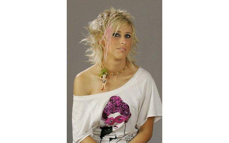 modella bionda indossa una maglia con una spalla scoperta