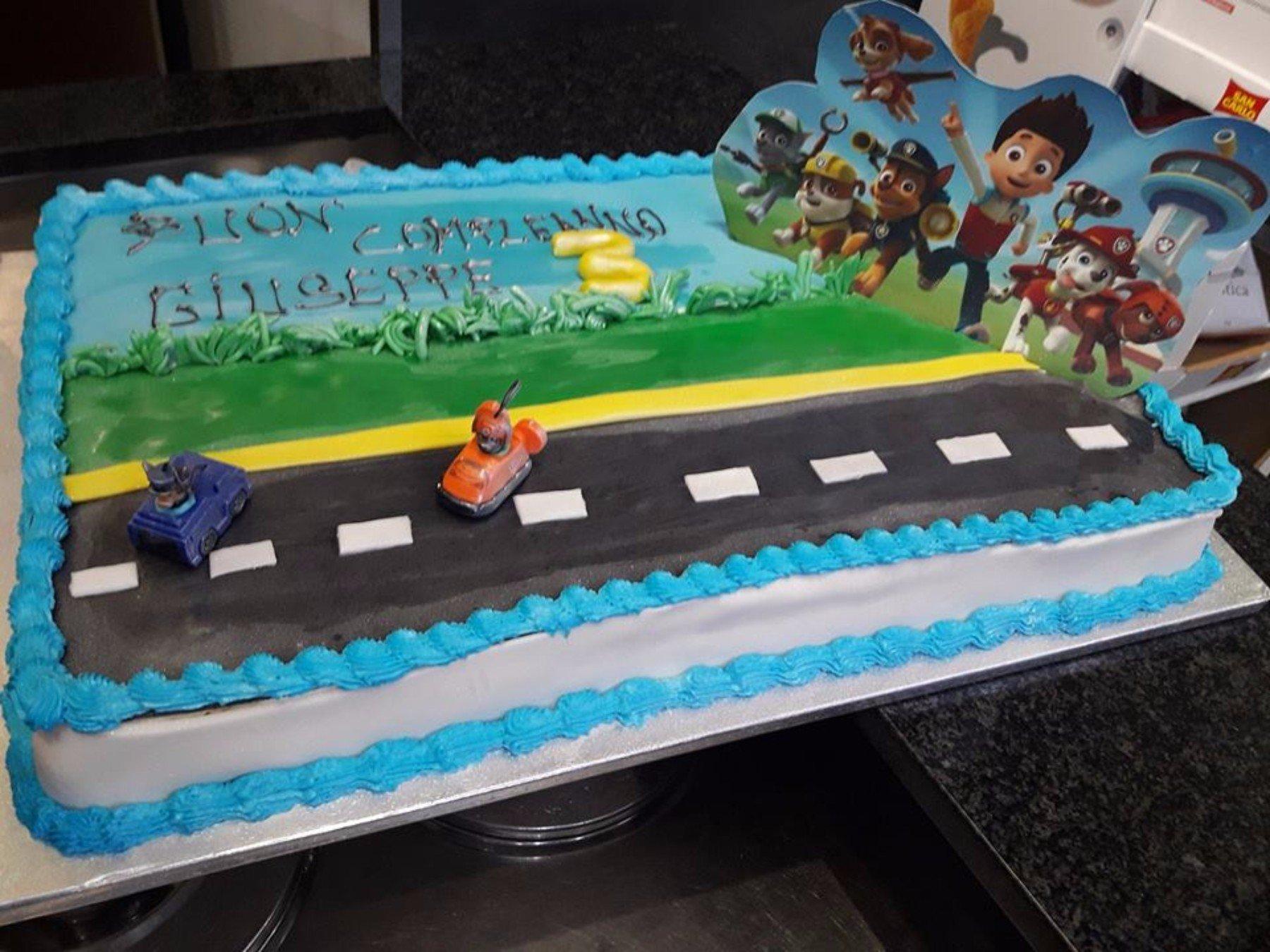 Torta blu e bianco con auto e personaggi di cartoni animati