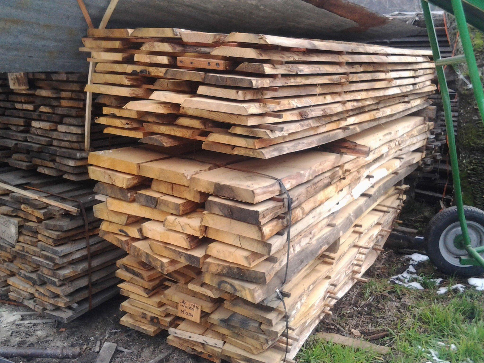insieme di legna tagliata e accanto la ruota di un carrello in ferro verde