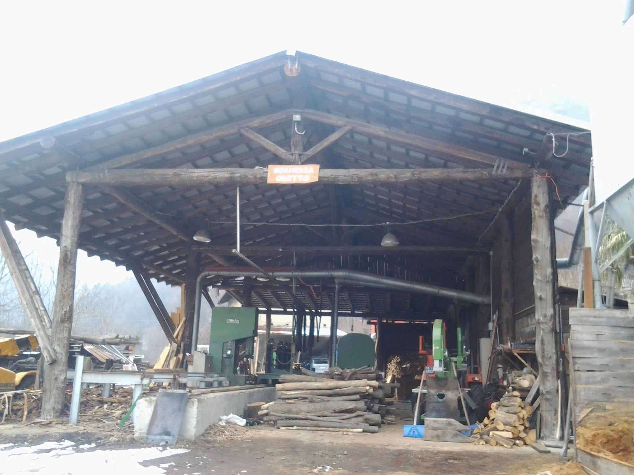 una segheria all'aperto con tetto in legno e legna e macchinari sotto