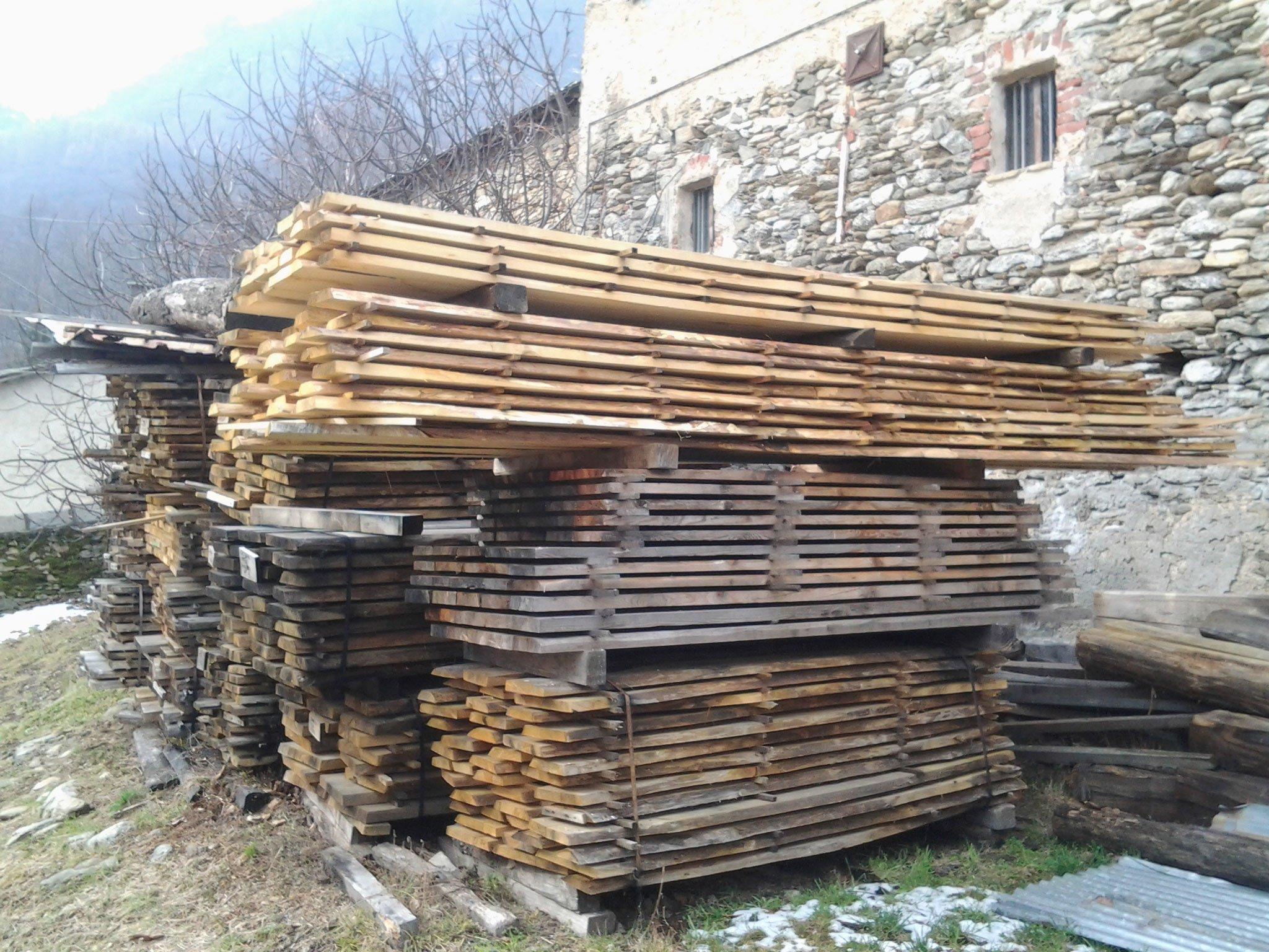 un insieme di legna tagliata vicino a una costruzione in pietra